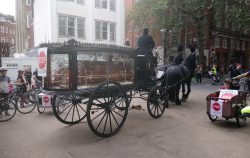A horse drawn funeral carriage awaited